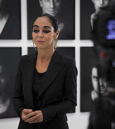 Portrait of the artist Shirin Neshat standing in Mathaf: Arab Museum of Modern Art, while being interviewed alongside a backdrop of her art