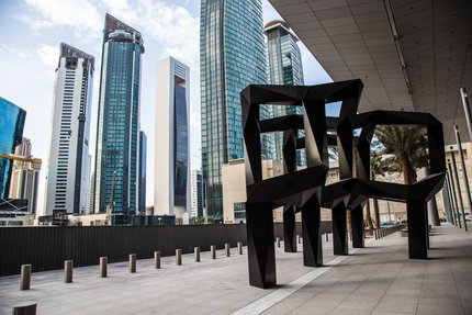 A view of Smoke, a black metal geometric sculpture by American artist Tony Smith in Doha with tall buildings in the background