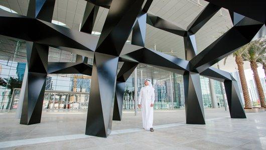 A wide shot of a man standing under the public art sculpture