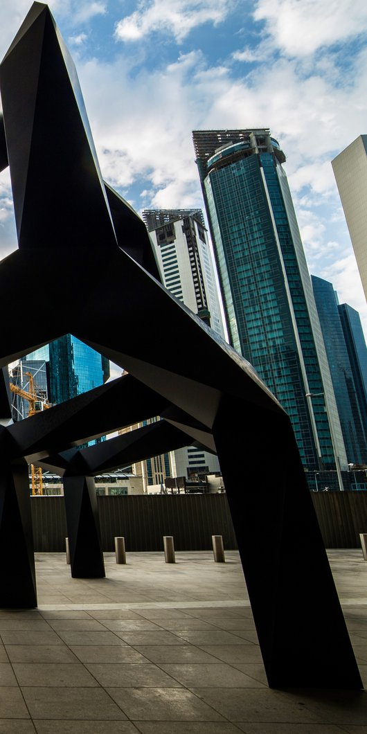 A view of Smoke, a black metal geometric sculpture by Tony Smith set against a backdrop of tall buildings in Doha
