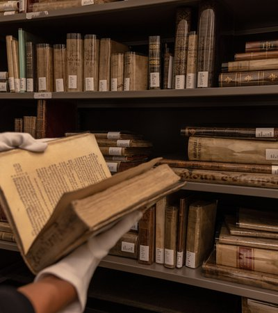 Person wearing white gloves and holding an antique book in front of library book shelves at the Museum of Islamic Art, Qatar