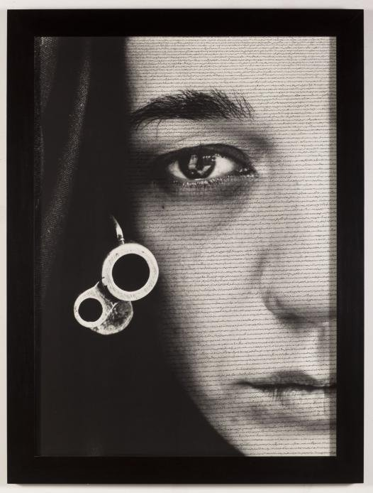 Black and white photograph depicting a frontal side portrait of an expressionless woman, while having Arabic calligraphy written on her face
