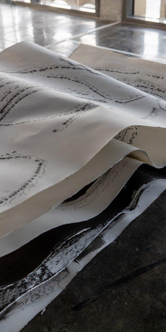 """عمل فني تم وضعه على الأرضية و هو مصنوع من مواد مختلطة يسمى """"بيان رقم 1 – في ذكرى (بيت رقم 10)"""" لأميرة العجي، مطافئ، الدوحة."""