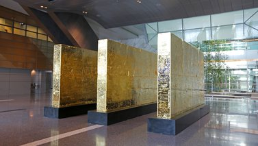 Three thick golden walls in the middle of the lobby at Hamad International Airport