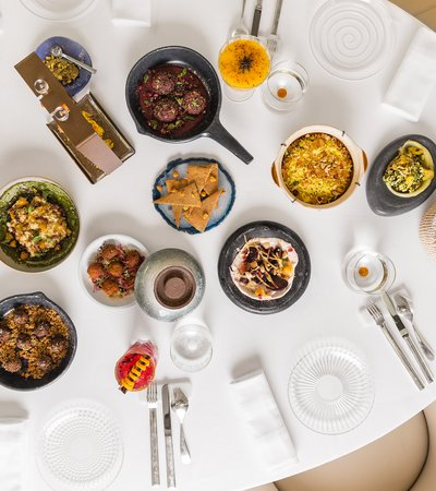 An view of a restaurant table seen from overhead with many colourful plates of traditional foods displayed