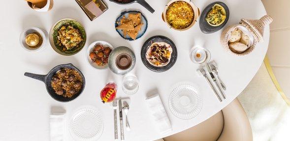 صورة علوية تظهر طاولة مطعم تضم عدداً من أطباق الطعام التقليدية التي يقدمها