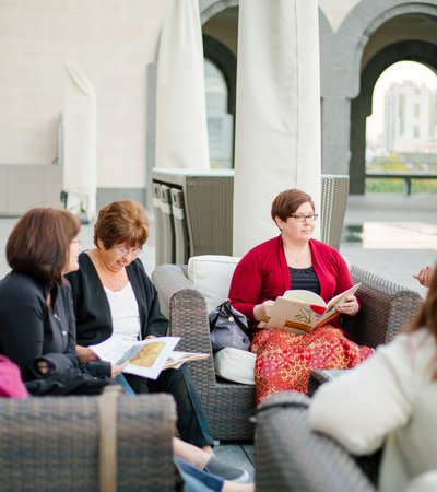A shot of women sitting at the MIA courtyard with open books in their hands