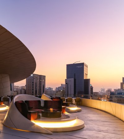 A view of the rooftop terrace seating at the Jiwan retaurant, National Museum of Qatar lit up at night with of Doha in the background