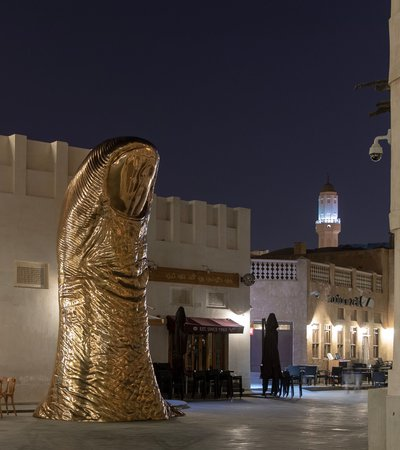 A bronze thumb sculpture in the middle of Souq Waqif, with a number of buildings and cafes in the background.