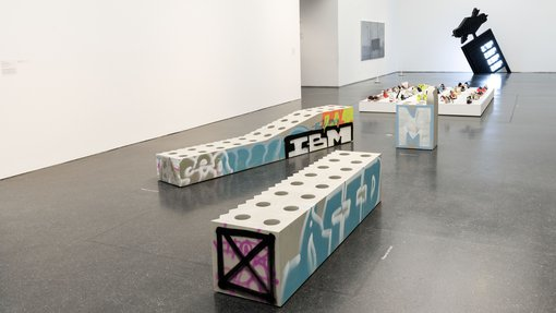 """Image of artwork by Virgil Abloh, """"Efflorescence (Bench 1 – Short Bench)"""" made of concrete and graffitied, on a gray museum floor"""