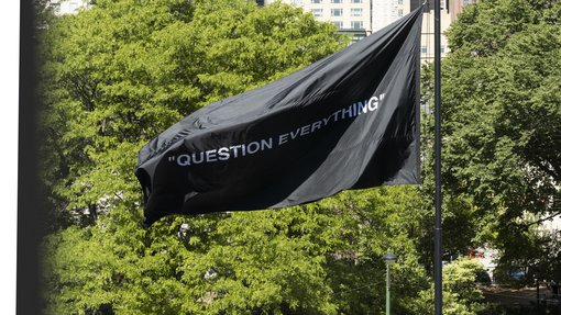 """Picture of a black flag with the words """"Question Everything"""" against a background of green trees and buildings"""