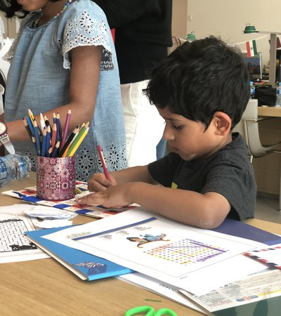 Two children colouring on a piece of paper with coloured pencils and books surrounding the desk