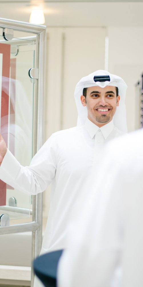 A man in traditional Qatari attire shows visitors some Arabic calligraphy